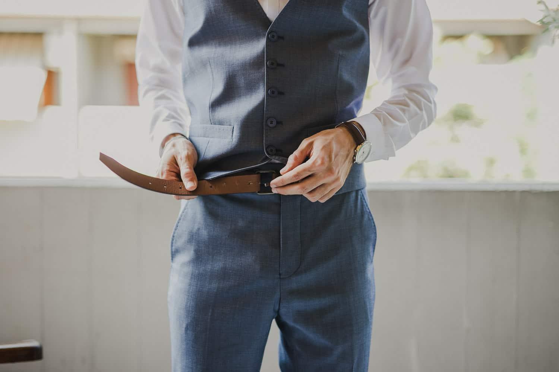 Lo sposo indossa la cintura color marrone per il suo abito blu.