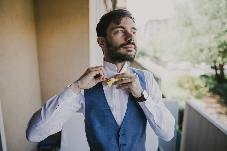 Lo sposo non ha scelto di indossare una cravatta per il suo matrimonio, ma un papillon giallo.