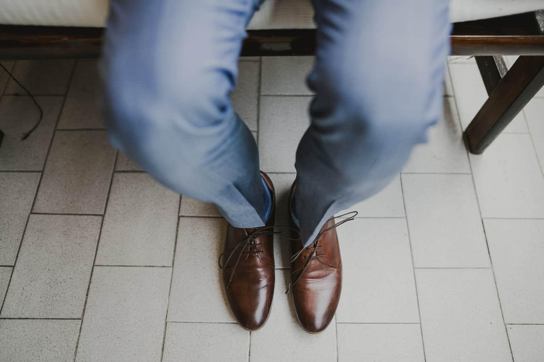 Lo sposo indossa un abito blu e delle scarpe marroni.