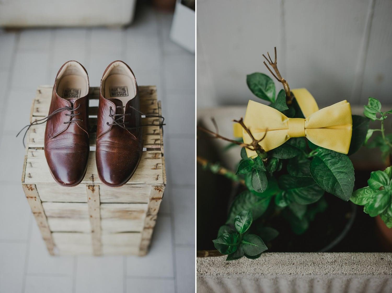 Le scarpe e il papillon giallo dello sposo sono appoggiati su una cassa in legno per una fotografia creativa.