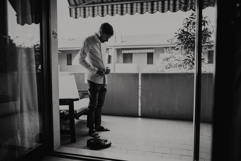 Lo sposo inizia la vestizione per il suo matrimonio. La fotografia è in bianco e nero.